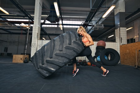 Foto de Fit female athlete working out with a huge tire, turning and flipping in the gym. Crossfit woman exercising with big tire. - Imagen libre de derechos