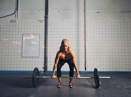 Photo pour Strong young woman lifting heavy weights at gym. Fitness female doing crossfit workout. - image libre de droit