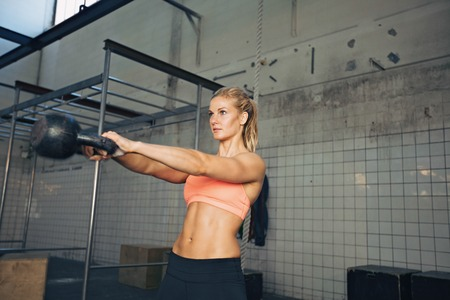 Photo for Fitness woman swinging kettle bell at gym. Young caucasian woman doing swing exercise with a kettlebell as a routine of a crossfit workout. - Royalty Free Image