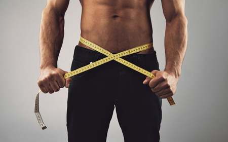 Photo pour Fitness man measuring his body. Cropped and mid-section image of young man measuring his waist with tape measure against grey background. Health and fitness concept. - image libre de droit