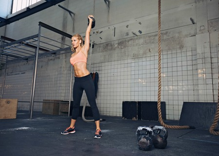 Photo for Young fitness woman lifting a heavy weight kettle bell at gym. Caucasian female athlete working out at gym. Fit young lady doing crossfit exercise. - Royalty Free Image