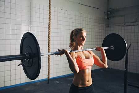 Foto de Strong woman lifting weights in cross-fit gym - Imagen libre de derechos
