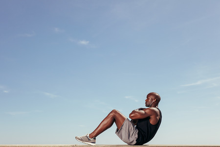 Photo pour Side view of fitness model doing crunches against blue sky. Young african man doing abdominal exercise outdoors. - image libre de droit