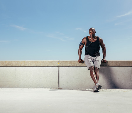 Photo pour Image of fit young man relaxing on embankment after his run against blue sky. African male athlete outdoors with copyspace. - image libre de droit