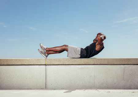 Photo for Athlete doing sit-ups against sky. African male model exercising outdoors with copy space.  - Royalty Free Image