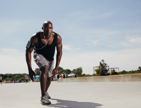 Photo pour Fit young man on his mark to start running. Determined athlete outdoors. Muscular african male model ready for his run on a hot summer day. - image libre de droit