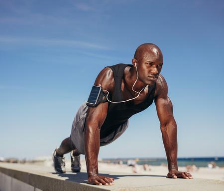 Photo pour Muscular man doing push ups against blue sky. Strong male athlete working out outdoors.  - image libre de droit