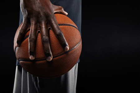 Photo pour Close-up of a hand of basketball player holding a ball against black background. - image libre de droit