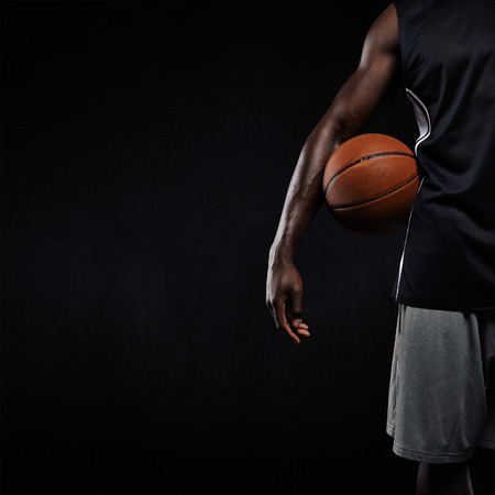 Cropped image of black basketball player standing with a basket ball. Man in sportswear holding basketball with copyspace on black background.