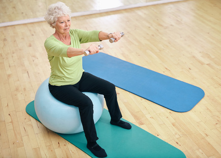 Foto de Senior female sitting on a fitness ball and lifting dumbbells. Old woman exercising with weights at gym. - Imagen libre de derechos