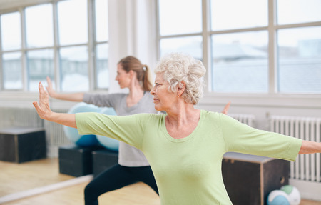 Foto für Two women doing stretching and yoga workout at gym. Female trainer in background with senior woman in front during physical training session - Lizenzfreies Bild