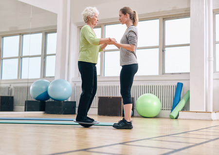 Photo pour Female trainer helping senior woman standing on a balance board at gym. Elder woman exercising being assisted by personal trainer. - image libre de droit