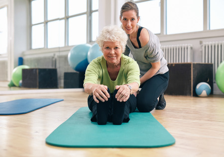 Foto de Senior woman sitting on exercise mat bending forward and touching her toes with her personal trainer assisting. Fitness training at gym with coach. - Imagen libre de derechos