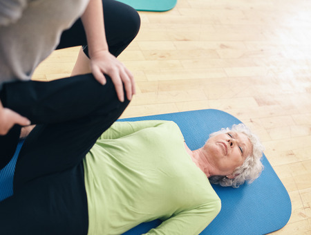 Senior woman lying on exercise mat with her personal trainer helping her doing leg stretches at gym. Elder woman receiving physical training from her personal trainer at rehab.