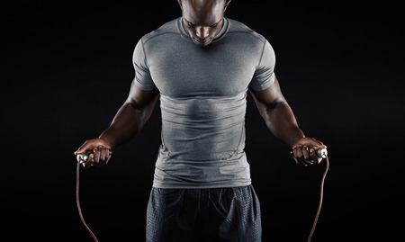 Foto de Muscular man skipping rope. Portrait of muscular young man exercising with jumping rope on black background - Imagen libre de derechos