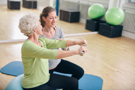 Foto de Senior woman exercising with weights in the gym assisted by a young female trainer. Old woman lifting dumbbells with help from personal trainer at rehab. - Imagen libre de derechos