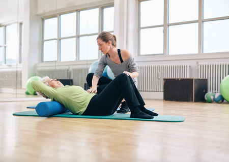 Photo for Senior woman performing back exercise on a foam roller being assisted by her personal trainer at gym. Physical therapist helping elder woman at rehab. - Royalty Free Image