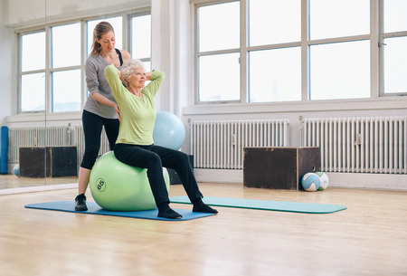 Photo pour Senior woman sitting on a pilates ball  exercising at health club being assisted by her personal trainer. Physical therapist helping senior woman in her workout at gym. - image libre de droit