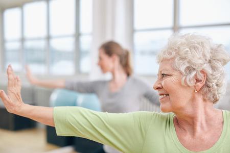 Foto de Close-up shot of elderly woman doing stretching workout at yoga class. Women practicing yoga at health club. - Imagen libre de derechos