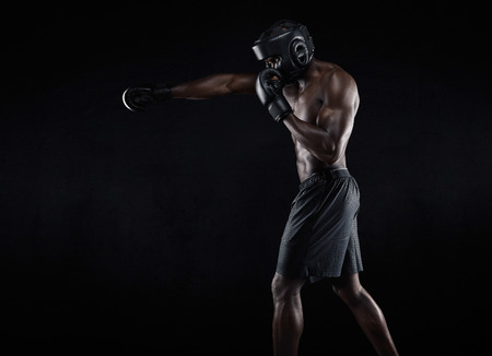 Foto de Side view of muscular man boxing on black background. Afro american young male boxer practicing shadow boxing. - Imagen libre de derechos