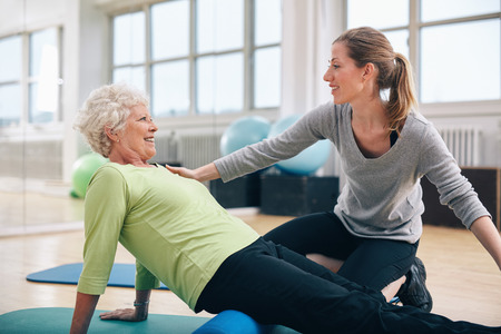 Photo for Physical therapist working with a senior woman at rehab. Female trainer helping senior woman doing exercise on foam roller at gym. - Royalty Free Image