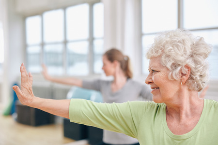 Indoor shot of senior woman doing stretching exercise at yoga class. Women practicing yoga at gym.