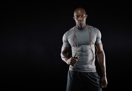 Photo for Studio shot of young african muscular man with jumping rope against black background. Fitness model with skipping rope around his neck with copy space. - Royalty Free Image