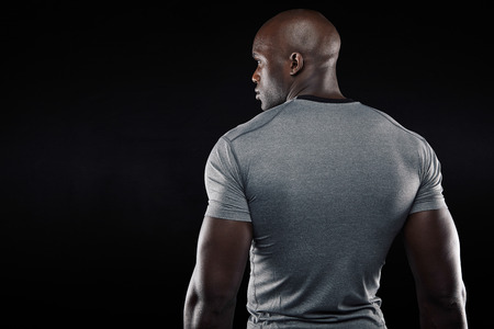 Photo for Rear view of fit young man with muscular build standing against black background. Afro american fitness model looking at copy space. - Royalty Free Image