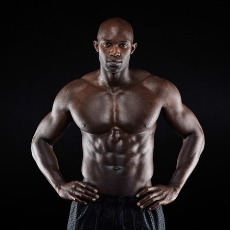 Photo for Portrait of a strong afro-american man showing off his physique against black background. Shirtless male model with his hands on hips. - Royalty Free Image