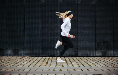 Foto de Side view of sporty young woman running on sidewalk in morning. Health conscious concept with copy space. - Imagen libre de derechos