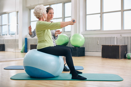 Photo for Female trainer assisting senior woman lifting weights in gym. Senior woman sitting on pilates ball doing weight exercise being assisted by personal trainer at health club. - Royalty Free Image