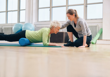 Foto de Senior woman exercising with a foam roller being assisted by personal instructor at gym. Physical therapist helping elderly woman in her workout at health club. - Imagen libre de derechos