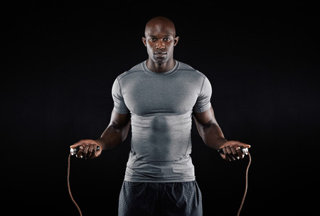 Photo pour Masculine man skipping rope in dark. Portrait of muscular young man exercising with jumping rope on black background - image libre de droit