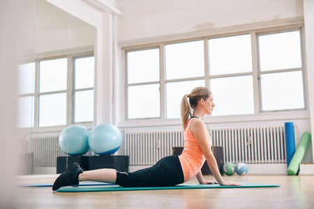 Photo pour Woman doing core stretch on fitness mat. Attractive young woman doing yoga at gym. - image libre de droit