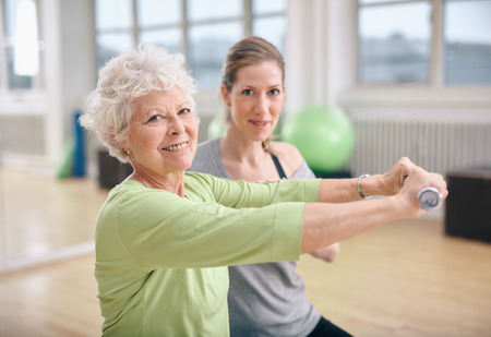 Photo for Senior woman exercising with fitness trainer at gym. Active senior woman lifting dumbbells with help from personal trainer. - Royalty Free Image