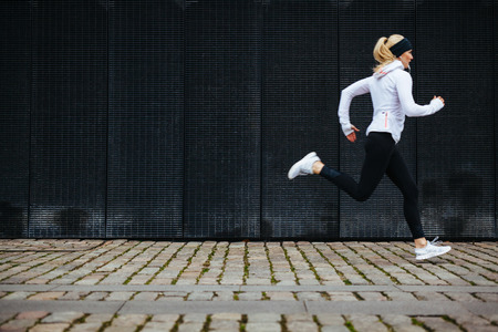 Foto für View of young woman running on sidewalk in morning. Health conscious concept with copy space. - Lizenzfreies Bild