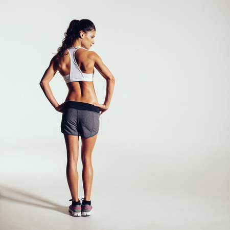 Foto für Rear view shot of a healthy young woman in sportswear. Full length image of muscular female model standing looking away at copyspace on grey background - Lizenzfreies Bild