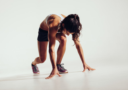Foto de Fit female athlete ready to run over grey background. Female fitness model preparing for a sprint. - Imagen libre de derechos
