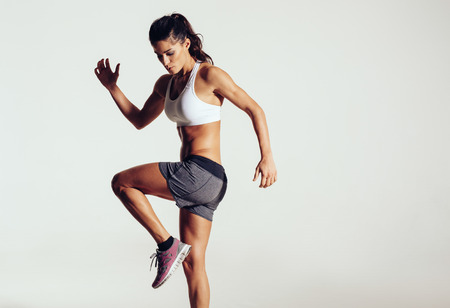 Foto de Attractive fit woman exercising in studio with copyspace. Image of healthy young female athlete doing fitness workout against grey background. - Imagen libre de derechos