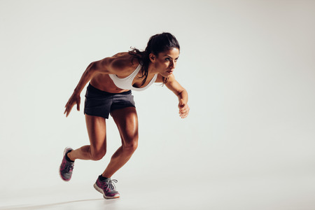 Photo pour Energetic young woman running over grey background. Focused young female athlete running. - image libre de droit