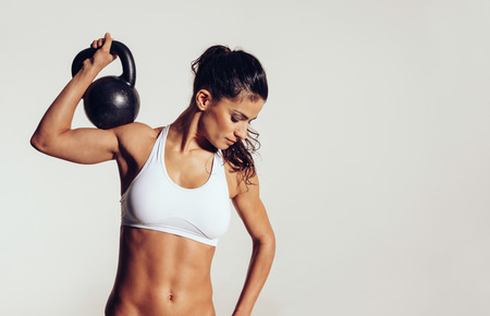 Foto de Attractive young athlete with muscular body exercising crossfit. Woman in sportswear doing crossfit workout with kettle bell on grey background. - Imagen libre de derechos