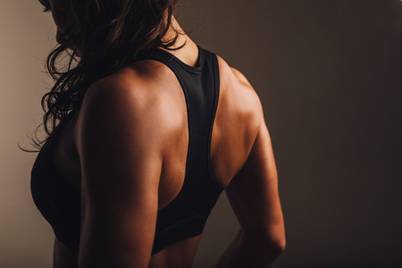 Foto de Rear view of strong young woman wearing sports bra. Muscular back of a woman in sportswear. - Imagen libre de derechos