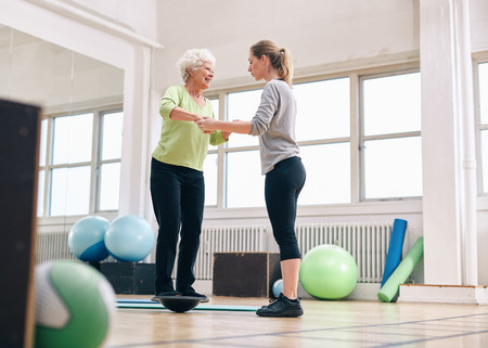 Photo pour Female trainer helping senior woman in a gym exercising with a bosu balance training platform. Elder woman being assisted by gym instructor while workout session. - image libre de droit