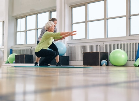 Photo for Senior woman doing exercise with her personal trainer at gym. Gym instructor assisting elder woman in her workout. - Royalty Free Image