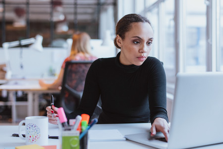 Photo for Image of young woman working on laptop while sitting at her desk in modern office. African female executive at work. - Royalty Free Image