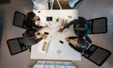 Foto de Overhead view of diverse team analyzing data while sitting at office. Multiracial business people in a meeting working on new project. - Imagen libre de derechos