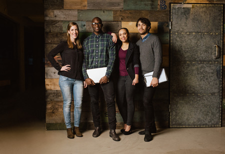 Foto de Portrait of successful business team standing together against wooden wall. Full length image of a group of diverse colleagues standing in an office - Imagen libre de derechos
