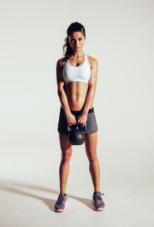 Photo for Fitness woman doing crossfit exercising with kettle bell. Beautiful fitness instructor on grey background. Female model with muscular fit and slim body. - Royalty Free Image