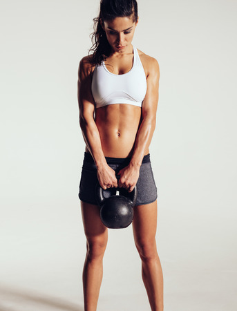 Photo for Fitness woman doing crossfit exercise. Tough fitness female model with kettle bell on grey background. - Royalty Free Image