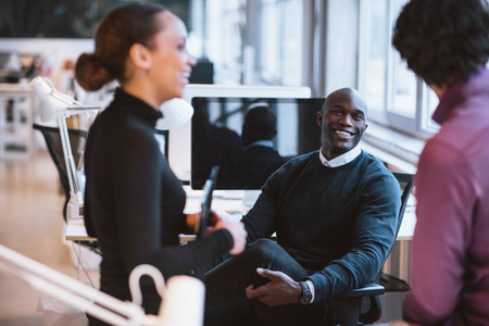Photo for Happy african man sitting at desk with coworkers smiling. Young business executives during break. - Royalty Free Image